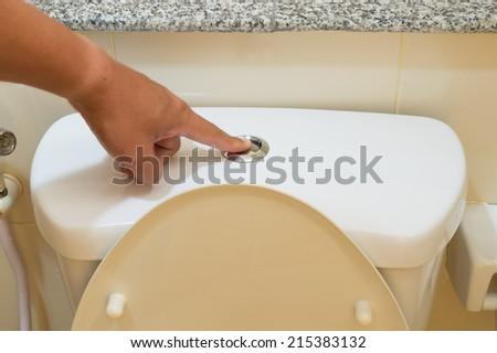 men finger pushing on button for flushing toilet - stock photo