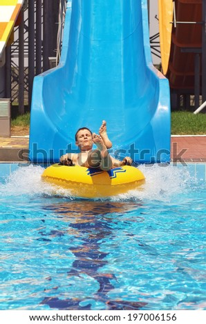 Men go down from water slide to swimming pool in aqua park. Happy men have fun on aqua park