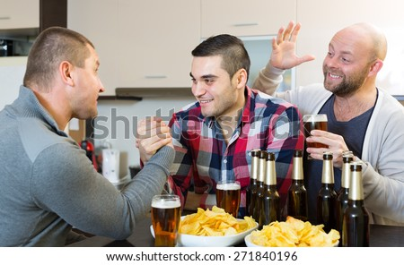 men having arm wrestling competition and laughing at house party - stock photo
