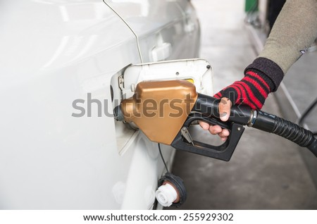 Men hold Fuel nozzle to add fuel in car at filling station - stock photo
