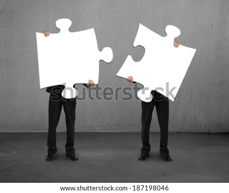 Men holding two puzzles concrete background
