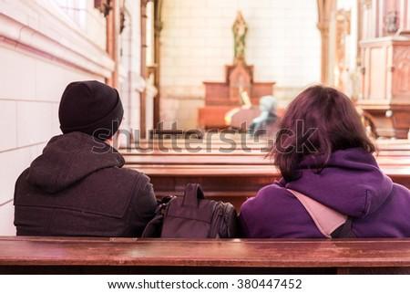 men in church interior sitting back on praying. - stock photo