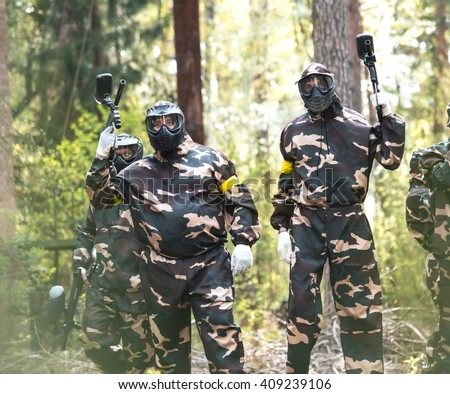 Men in protective suits and masks play paintball in the woods in summer