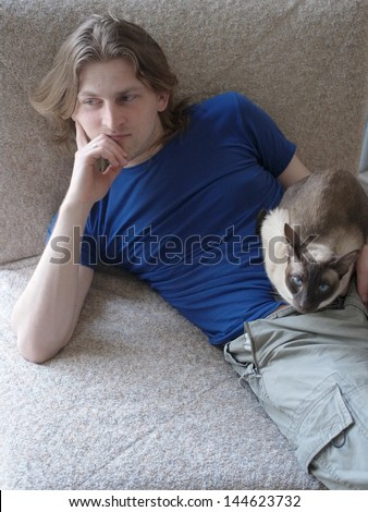 Men in sitting in the couch with a cat