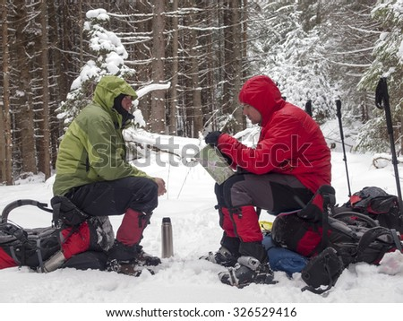 Men in snowshoes sit on backpacks and watch the map in the winter forest.