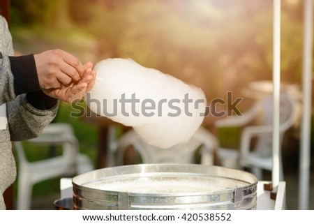 Men is preparing candy floss in the park. Children Day - stock photo