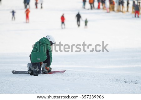 Men is preparing to do snowboarding  - stock photo