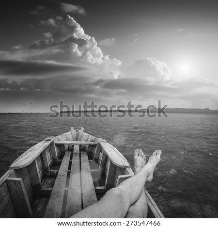 Men on vacation, siting in a old rustic boat on a river and enjoy beautiful sunset. Black and white