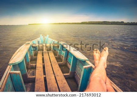 Men on weekend, sitting in a old rustic boat on a river and enjoy sunrise - stock photo