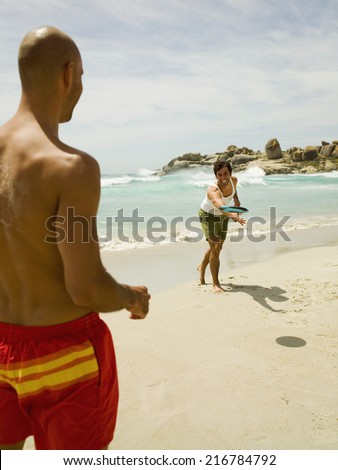Men playing frisbee on the beach. - stock photo