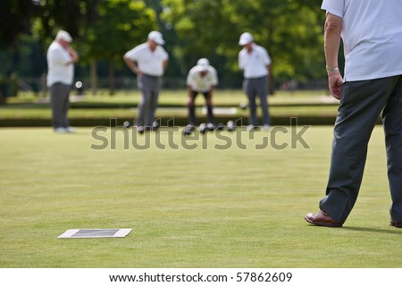 Men playing lawn bowls. Narrow depth of field. - stock photo