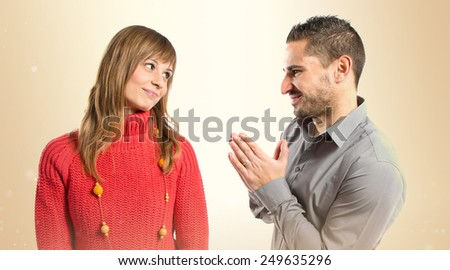Men pleading at his girlfriend over ocher background