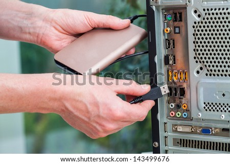 Men plug in a portable hard drive - stock photo