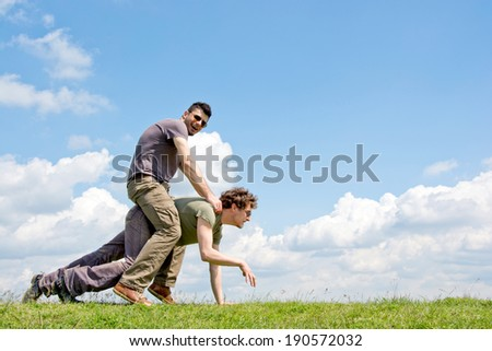 Men riding one over another with fluffy clouds in background - stock photo