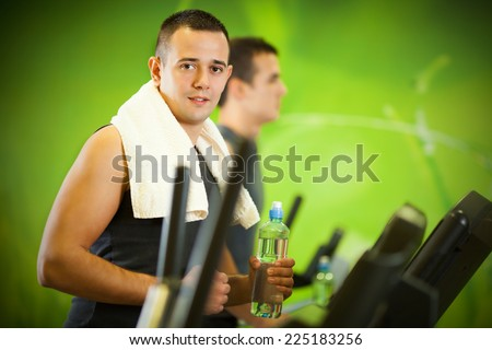 Men running on treadmill at the gym - stock photo