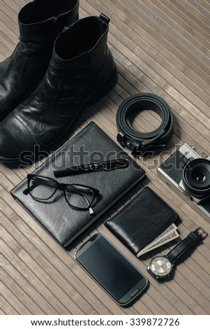 Men's accessories, black leather shoes, belt, black leather book, pen, glasses, camera, wristwatch, wallet, money, smart phone, on a bamboo background - stock photo