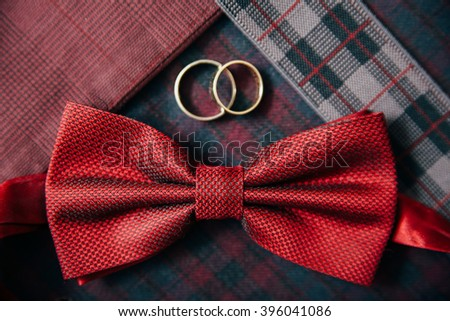 Men's accessories - bow tie, wedding  rings, cufflinks on textile background. - stock photo
