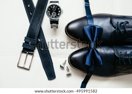 Men's accessories men's shoes, watches, glasses, bow tie, sleeve shirt and strap. Black and white minimalistic composition on a white background. Classic men's accessories. Top view