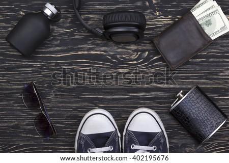 Men's accessories: wallet, headphones, sunglasses, perfume, flask and sneakers. - stock photo