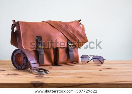 Men's accessories with brown leather bags, belt and sunglasses on wooden table over wall background - stock photo