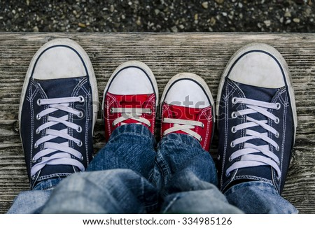 Men's and children's branded shoes together. - stock photo