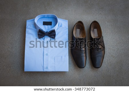 Men's casual, blue shirt with bow tie and black man's shoes on gray background  - stock photo