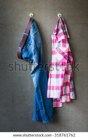 Men's casual outfits, blue jeans and pink plaid shirt hanging over gray grunge background - stock photo