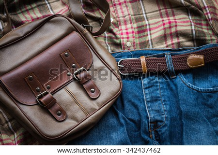 Men's casual outfits, blue jeans, brown plaid shirt and bow tie and brown bag - stock photo