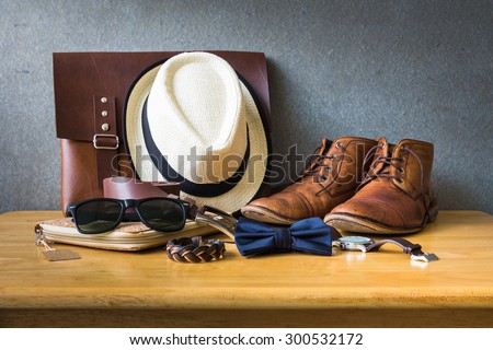 Men's casual outfits on wooden table over wall grunge background - stock photo
