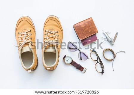 Men's casual outfits with brown shoes and passport, travel preparations and accessories on white background