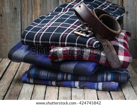 Men's clothes, neatly stacked on wooden background