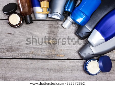 Men's cosmetics background. Various cosmetic products for men laid out as semicircular frame on old wooden planks. Copy space - stock photo