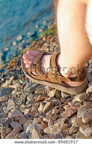 Men's feet in the open summer shoes on the stone the beach - stock photo