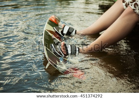 Men's feet on a wakeboard in water.guy sitting by the river and is preparing to go wake boarding - stock photo