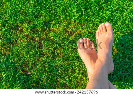 Men's feet on the background of lush green grass - stock photo