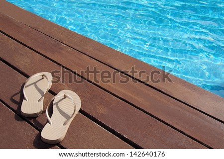 Men's flip-flops by the swimming pool - stock photo