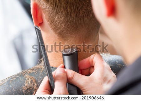 men's haircut with clipper in the barber shop - stock photo
