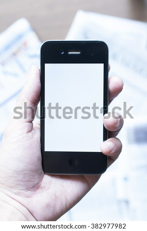 Men's hand holding smart phone with blur newspaper background ebook concept  - stock photo