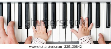 Men's hand on electric piano, next to a child's hand