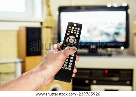 Men's hand sends the remote control on the TV in the living room - stock photo