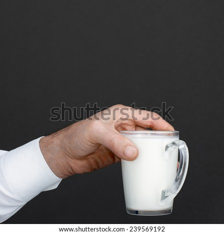 Men's hand with a cup of milk in a dark background