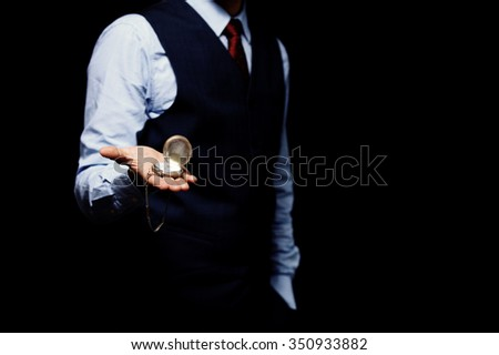 men's hand with a watch isolated on black - stock photo