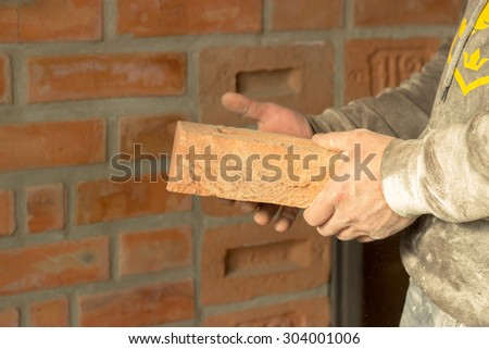 Men's hands are kept carved brick on brick wall background, man's hands are kept brick and hammer