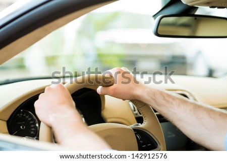 Men's hands hold a wheel of a car, the car in the showroom assessment