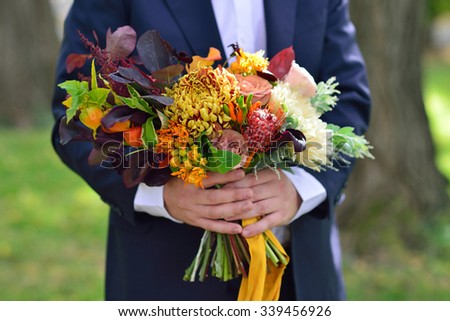 Men's hands hold the bridal bouquet - stock photo