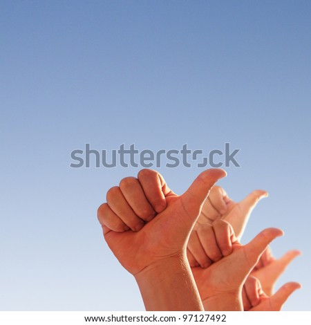 men's hands make thumbs up on blue sky - stock photo