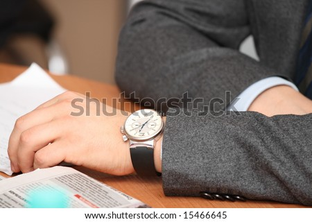 men's hands with watches on the table - stock photo