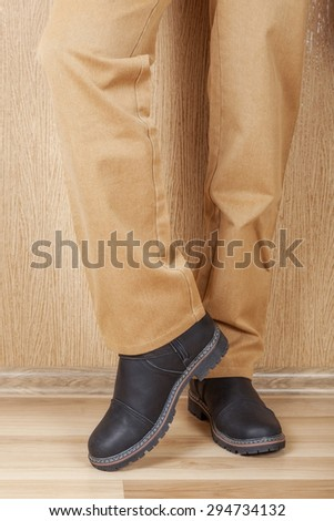 Men's leather shoes and jeans khaki legs. A man stands on a wooden floor near the wall. - stock photo