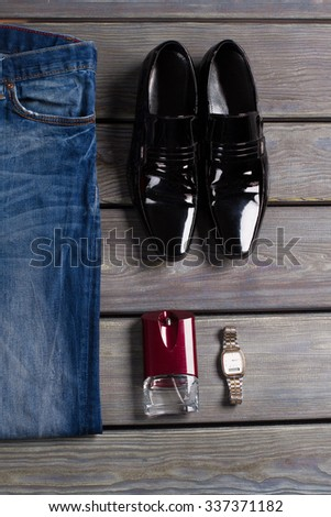 Men's patent-leather shoes, jeans and accessories. - stock photo