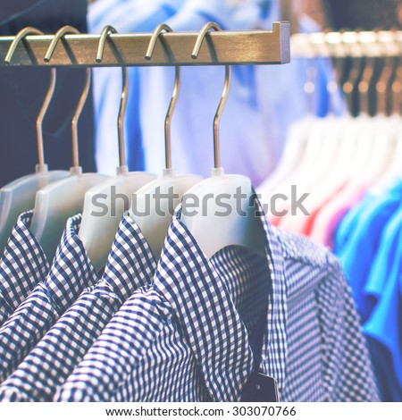 Men's plaid shirts on hangers in a retail shop - stock photo